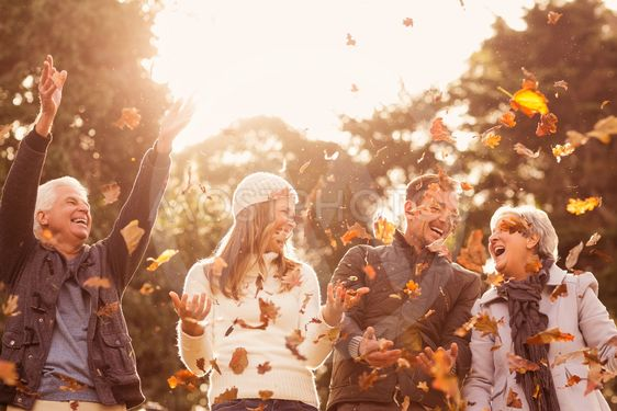 Happy family throwing leaves around