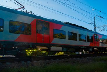 The red-grey train sweeps through the resort town, the...