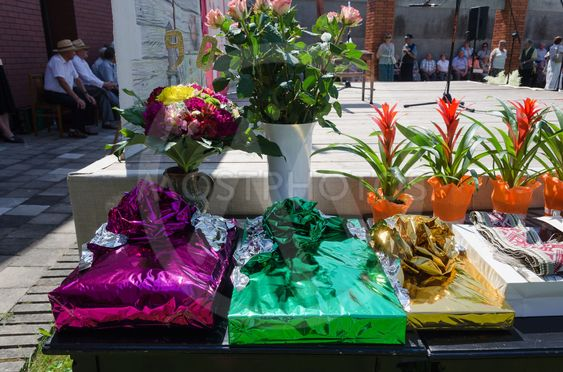 gift in glossy paper and bouquets on table outdoor