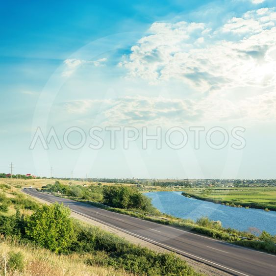 sunset in clouds over river and asphalt road