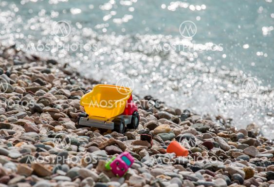 Bright plastic baby toy cars on a pebble beach near the...