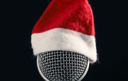 Close up of a microphone with the hat of Santa on a dark...