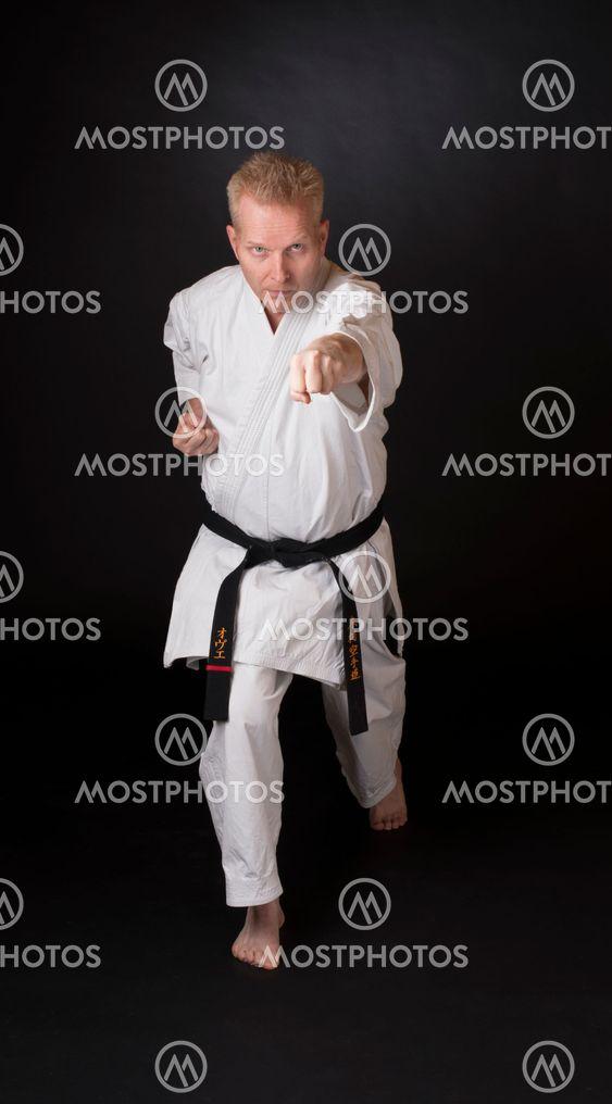 En man i karate-dräkt med svart bälte visar en karate...