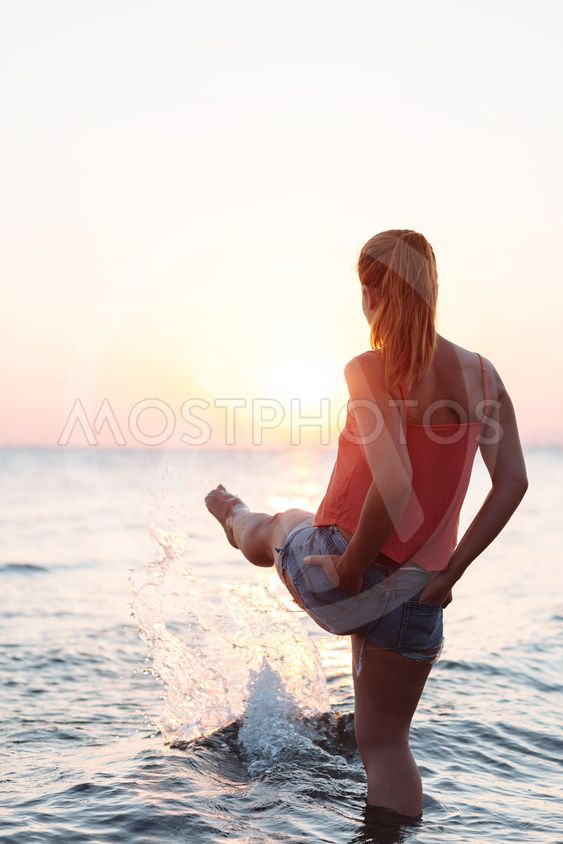 Young woman enjoying sea and sunset