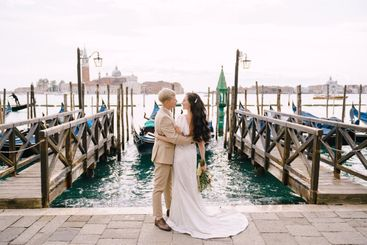 Groom and stand next to the gondola pier, hugging, in...