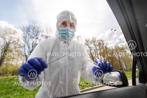 healthcare worker making coronavirus test at car