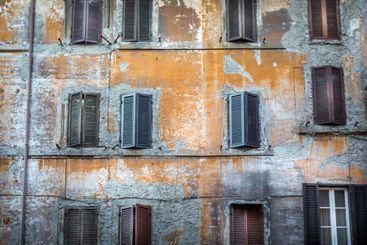 Sliten byggnad med många fönster och fönsterluckor..