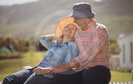 Smiling senior couple relaxing together on bench