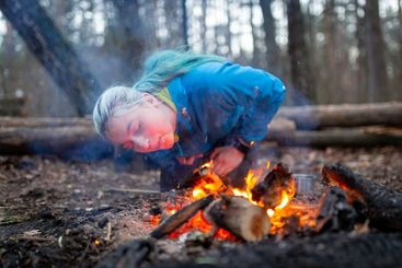 Woman blowing a fire with sparks in forest outdoor camping