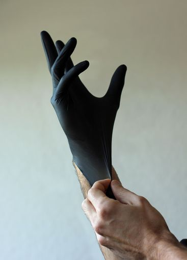 Putting on black disposable gloves for prevention