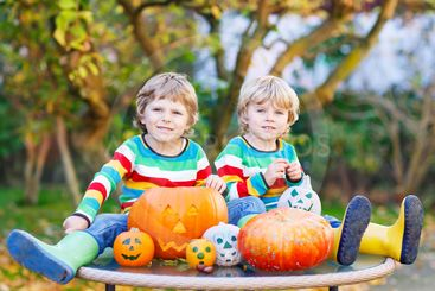 Two little friends boys making jack-o-lantern for...