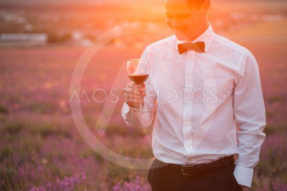 Elegant young guy drinking wine on sunset