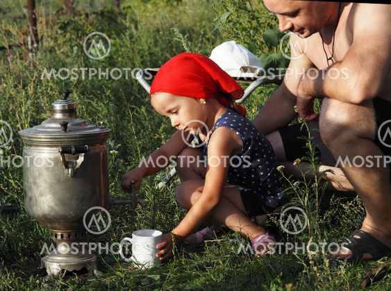 A little girl, while relaxing with her dad in nature,...