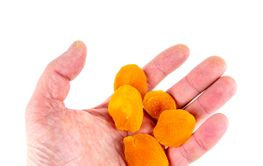 Dried apricots in a hand on a white background with...