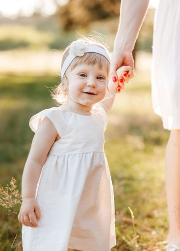 View on toddler. mother holds hand daughter enjoy nature...
