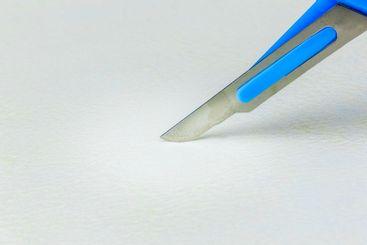 Närbild på vass skalpell mot ljust underlag.