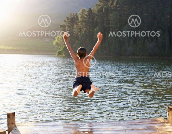 Young boy jumping into lake
