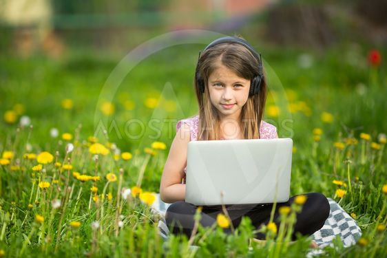 Little girl in headphones with laptop sitting on the...