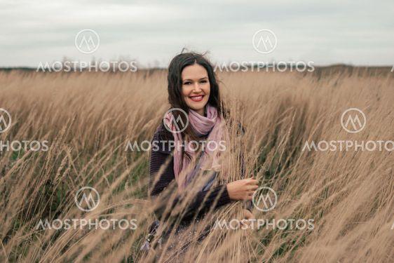 beautiful young woman standing among ripe ears of wheat