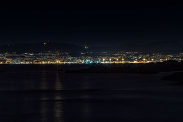 A night shot of a city skyline in Spain