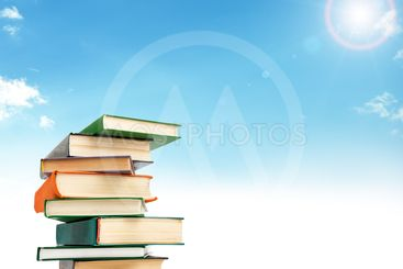 A stack of books on white floor against blue sky