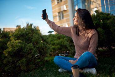 Smiling female brunette posing for selfie on a dooryard...