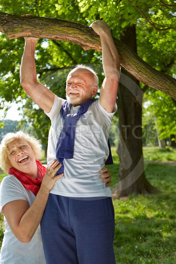 Old man doing pull-ups on a tree