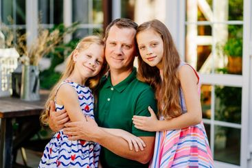 dad hugs two cute daughters in garden of house.
