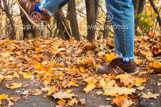 Womans leg kicks yellow autumn leaves from the ground in...