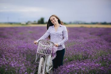 beautiful young Woman with retro bicycle in lavender...