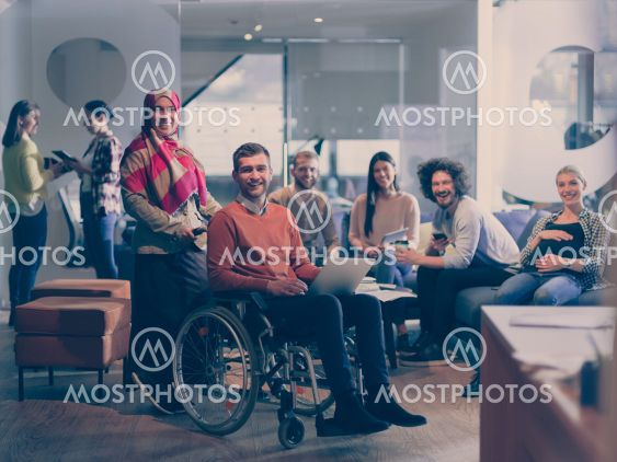 Disabled businessman in a wheelchair at work in modern...