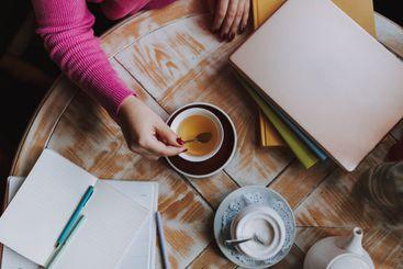 Female student stirring tea with a teaspoon indoors