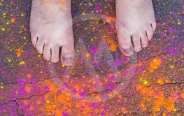 Barefoot person standing in colorful Holi powder
