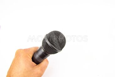 Black microphone in a man's hand on a white background.