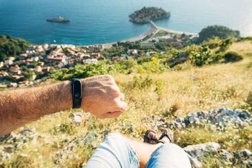 Fitness bracelet on a man's hand. A man sits on top of a...