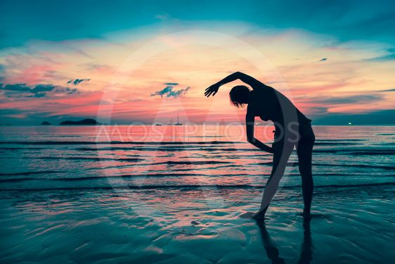 Woman doing exercises on the beach during sunset....