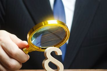 A man examines a paragraph figure with a magnifying...