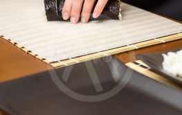 Closeup of woman chef cutting japanese sushi roll