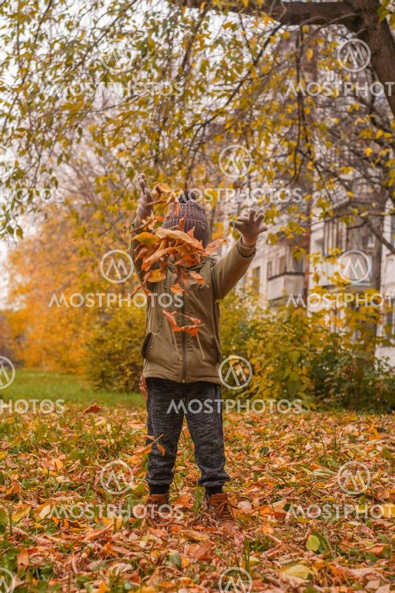 Little boy tossing leaves in autumn park.