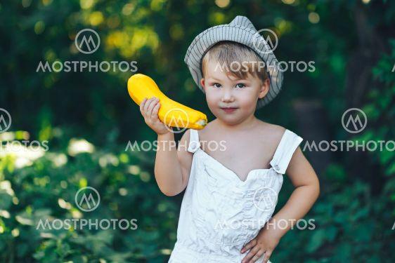 little boy holding yellow zucchini squash in summer...