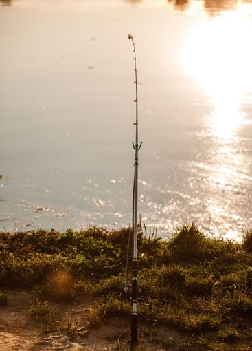 sunset fishing. fisher with spinning rod. Fisherman with...