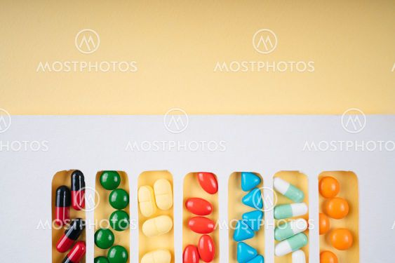 Colourful pills in white frame over yellow background.