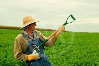 farmer in his hay field playing air guitar
