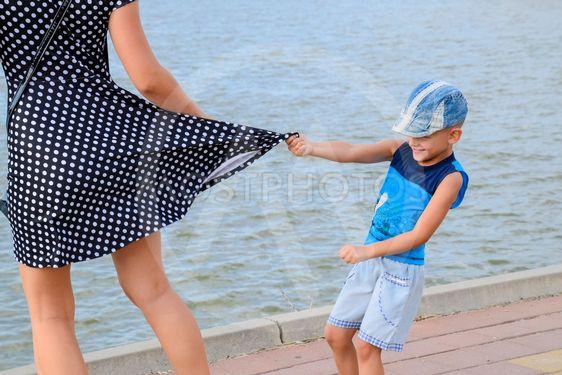 The little boy looks under his skirt. Children's pranks....