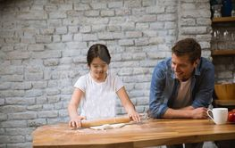 Father and daughter making bread in the rustic kitchen