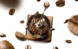 Coffee grinder and coffee beans in flight on white...