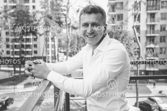 stylish smiling man in white shirt posing on balcony...