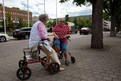 Två äldre damer med rollator diskuterar
