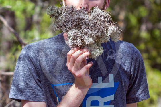 Young man holding lichen as fake beard