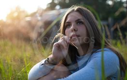 Teenage girl sitting in green grass in summer countryside.